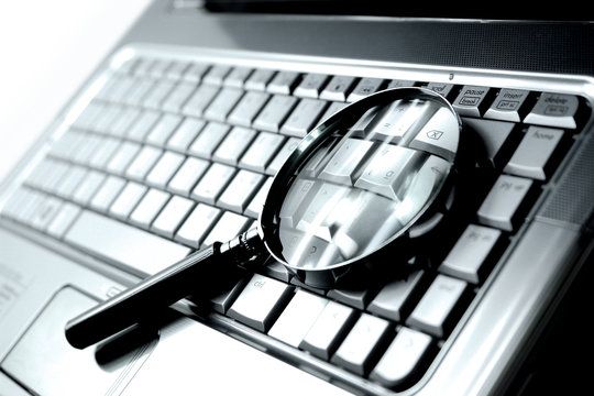 Laptop computer with magnifying glass, concept of search.