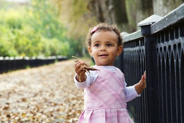 cute happy baby girl playing with autumn leaves