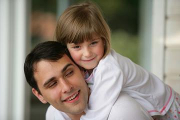 homme souriant portant une petite fille sur son dos