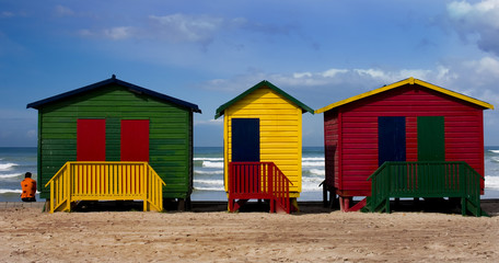 Colorful painted beach huts with lone figure staring at ocean