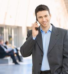 Happy businessman talking on mobile