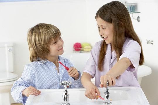 Siblings Brushing Teeth Together at Sink