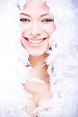 portrait of laughing young woman in white downy boa