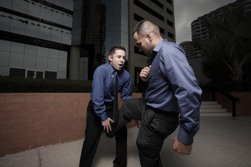 Businessman kicking another businessman
