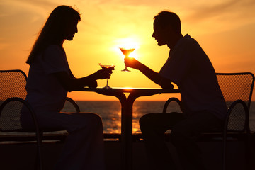 Female and man's silhouettes on sunset sit at table with two gla