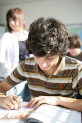 Portrait d'un jeune garçon assis en salle de cours