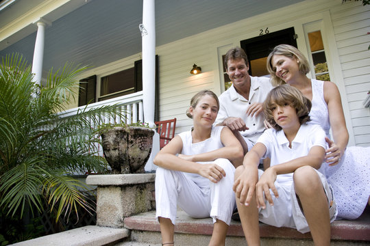 Family sitting together on front porch steps
