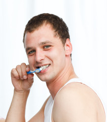 Attractive man cleaning teeth