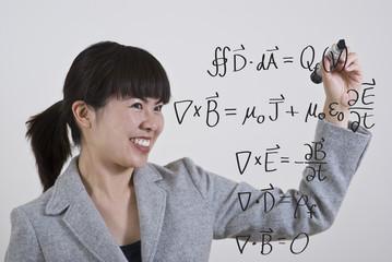 woman writing maxwell equations