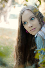 Beautiful blue eyed woman portrait with the park as background.