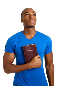 Student holding a bible looking up