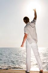 Fototapeta Man at the beach rising the hand