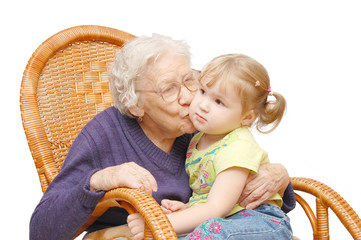 Grandmother kisses the granddaughter in an armchair