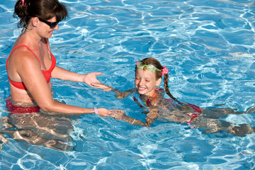 Child learn swim in swimming pool.Outdoor.