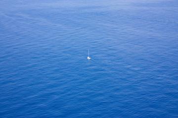 Single boat sailing in a vast ocean