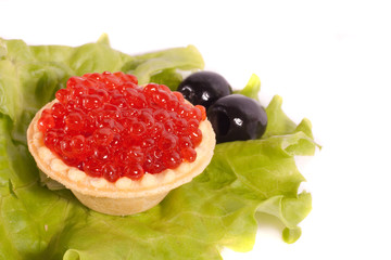 Caviar on sheet of salad with olives