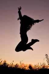 silhouette of young woman jumping