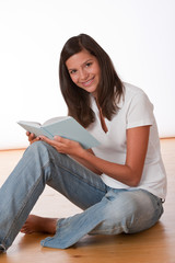 Happy teenager sitting with book
