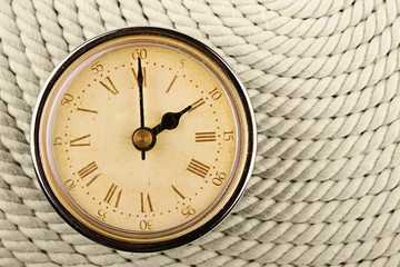 Clock with Roman numerals on cord background. 2