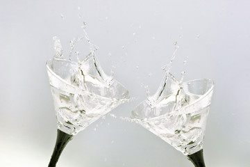Two glasses with alcohol splashing