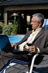 Businessman with laptop and glass of wine