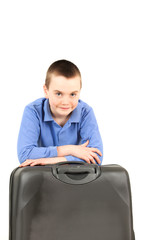 Portrait of young boy waiting with suitcase, studio shot