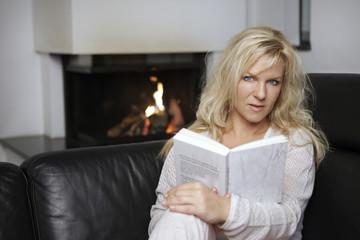 Frau vor Kamin liest ein Buch