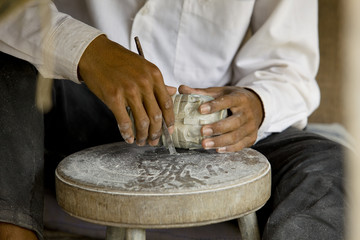 male hands carving a stone in cambodia