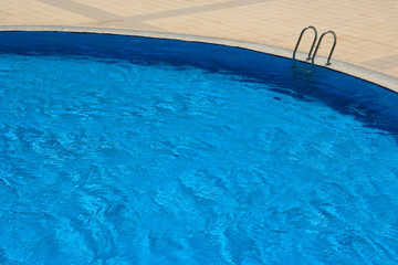 An image of blue swimming pool in summer