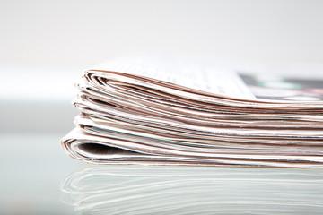 Tageszeitungen auf einem Glastisch