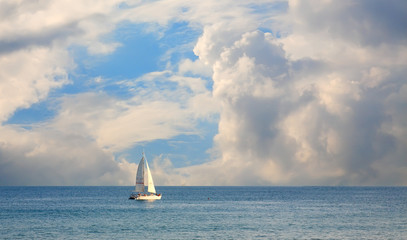 sailing yacht floating on the sea against the big white clouds.