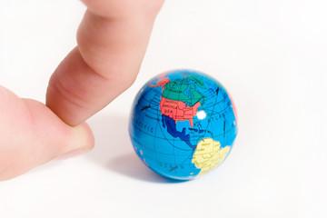Human fingers ready to push a small globe