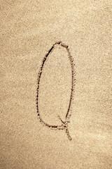 Alphabet letter Q handwritten in sand