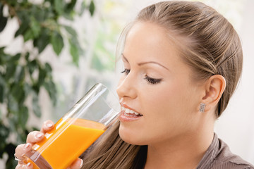 Young woman drinking orange juice
