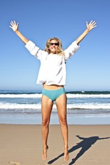 Young beautiful blonde woman making a jump out of joy