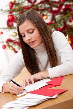 Young woman writing Christmas card