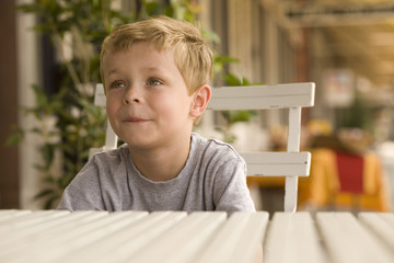 Young Boy Sitting at Outdoor Table