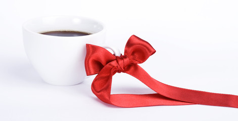 White cup of coffe with red bow