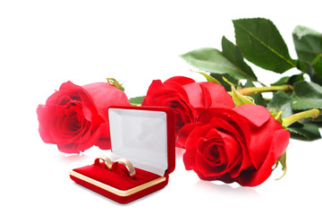 Red rose and wedding rings isolated on white