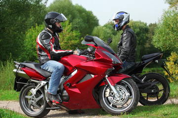 two motorcyclists standing on country road, side view