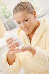 Woman using body lotion