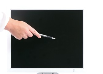 Hand with pen showing something on computer monitor