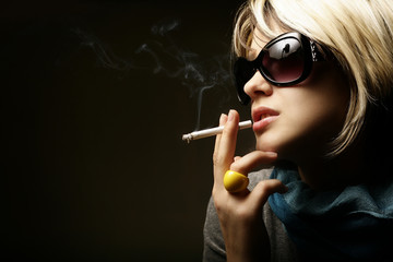 The beautiful girl smokes a cigarette