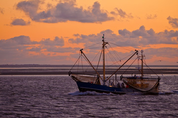Sunset at sea with a fishing boat in the front