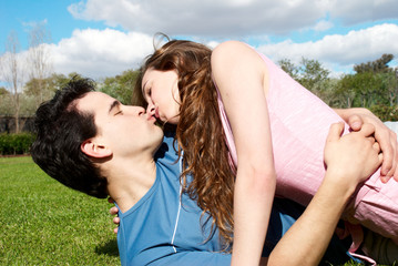 Happy young couple kissing at park in grass