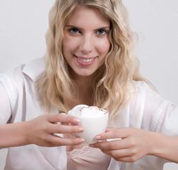 Blonde Frau mit Kaffee und Milchschaum