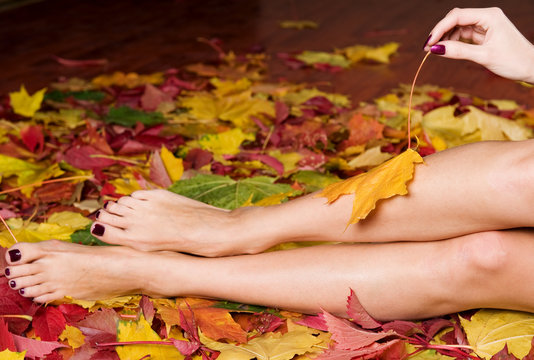Beautiful woman manicure and pedicure in autumn leaves