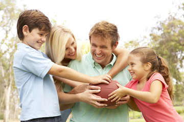 Family Playing American Football Together In Park