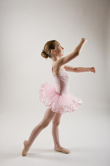 young girl practicing ballet dressed in pink tutu
