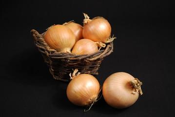 Ungeschälte Zwiebeln im Korb und davor